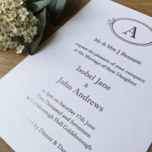 A silver monogram invitation