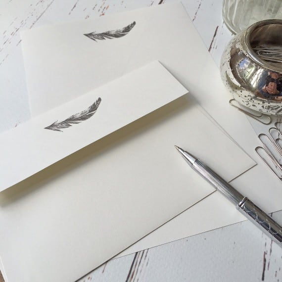 Writing paper with a Feather illustration